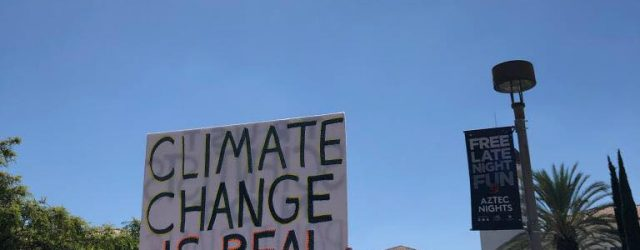 "Person holds ""CLIMATE CHANGE IS REAL"" sign while walking towards the Conrad Prebys Aztec Student Union"