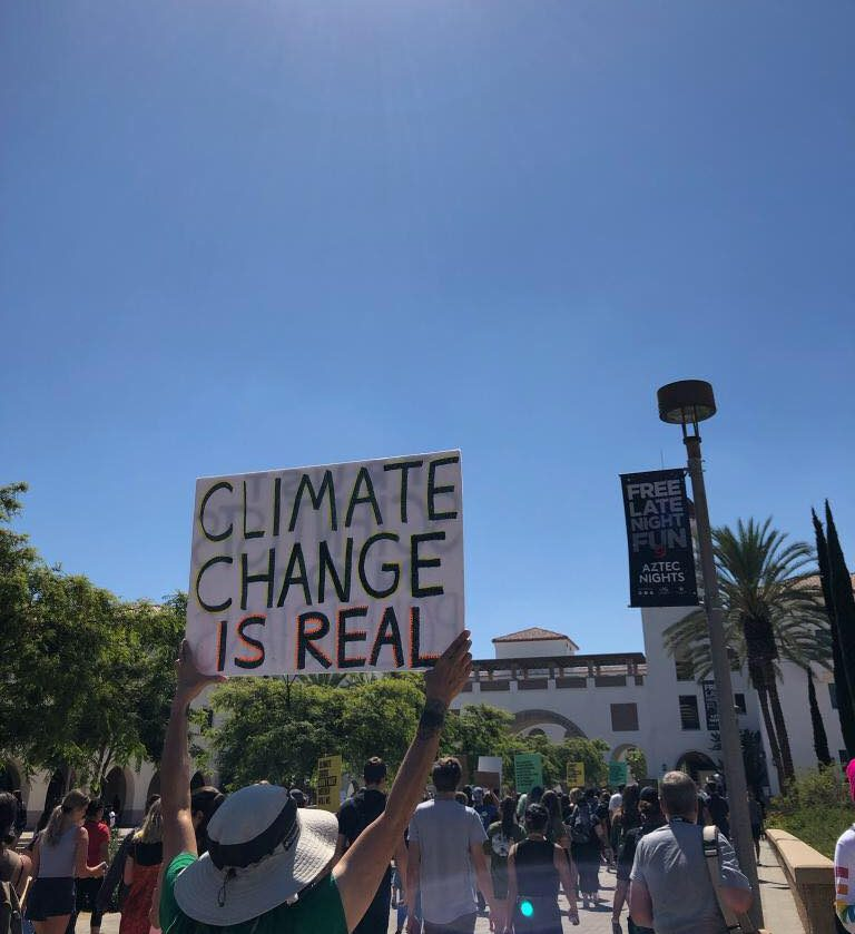 """Person holds """"CLIMATE CHANGE IS REAL"""" sign while walking towards the Conrad Prebys Aztec Student Union"""