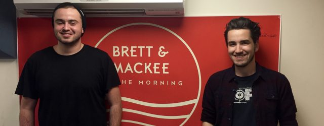 Brett and Mackee pose in the KCR Studio in front of their banner.