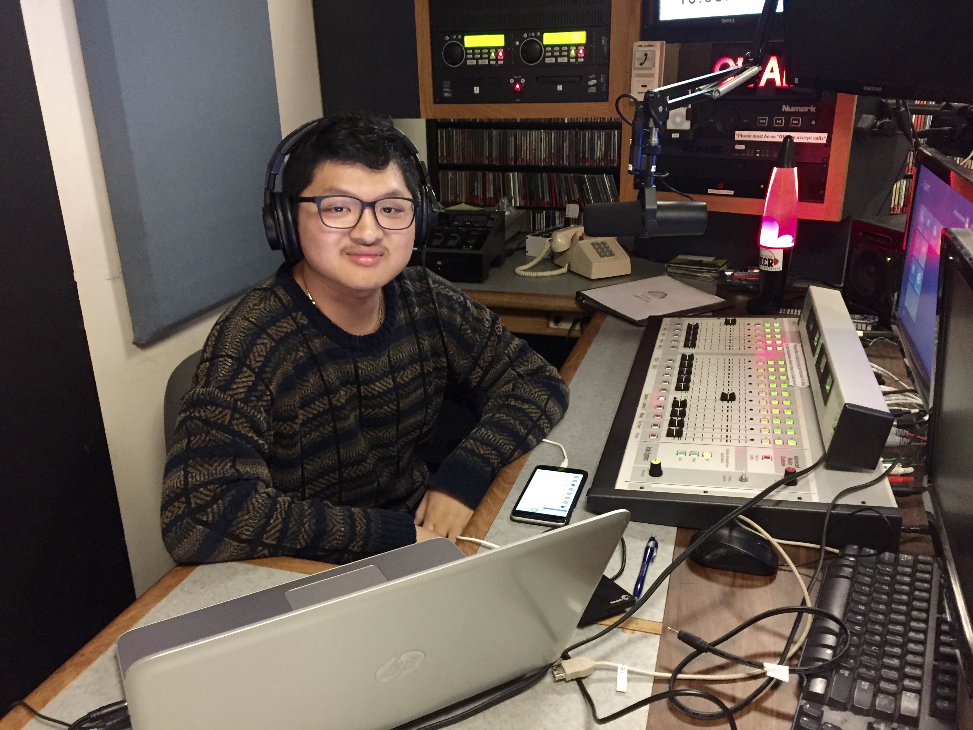 Christian Le, a music DJ at KCR, begins his playlist for the night in the studio.